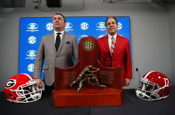 Georgia head coach Kirby Smart, left, and Alabama head coach Nick Saban pose near the Championship trophy, Friday, Nov. 30, 2018, in Atlanta. Georgia and Alabama will play Saturday in the Southeastern Conference championship NCAA college football game. (AP Photo/John Bazemore)