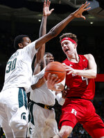 Rutgers' Paul Mulcahy, right, dishes off against Michigan State's Aaron Henry, center, and Marcus Bingham Jr. (30) during the first half of an NCAA college basketball game, Sunday, Dec. 8, 2019, in East Lansing, Mich. (AP Photo/Al Goldis)