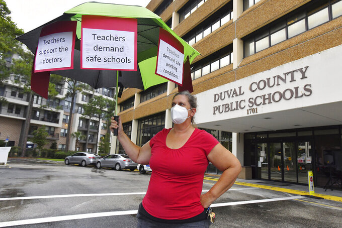 Christine O'Riley, a school teacher and the mother of a child under 12 holds her protest umbrella outside the school board building ahead of their Tuesday evening meeting to discuss the masking issue Aug. 3, 2021. Around 50 people gathered outside the Duval County School Board building in Jacksonville, Fla., in support of having mandatory masking of teachers and students ahead of the school board taking up the issue in their Tuesday evening meeting. Florida's Gov. Ron DeSantis has forbidden mandating masks in Florida's public schools despite CDC recommendations to wear masks due to the recent surge of COVID-19 infections which are particularly high in Northeast Florida. (Bob Self/The Florida Times-Union via AP)