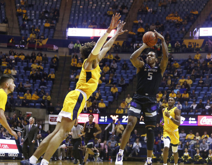 Kansas State guard Barry Brown Jr. (5) shoots while defended by West Virginia forward Emmitt Matthews Jr. (11) during the first half of an NCAA college basketball game Monday, Feb. 18, 2019, in Morgantown, W.Va. (AP Photo/Raymond Thompson)
