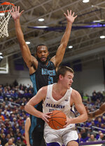 FILE - In this Dec. 15, 2018. file photo, Furman's Matt Rafferty works against North Carolina Wilmington's Jeantal Cylla during the first half of an NCAA college basketball game in Greenville, S.C. Eric Musselman, the new coach at Arkansas, relied heavily on transfers at Nevada and bolstered his new team with graduate transfers Cylla from UNC Wilmington and Jimmy Whitt Jr. The 6-foot7 Cylla can bang down low, but also step out at hit 3s. (AP Photo/Richard Shiro, File)