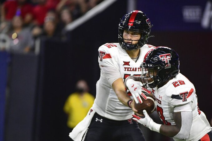 FILE - In this Saturday, Sept. 4, 2021, file photo, Texas Tech quarterback Tyler Shough (12) hands off the ball to running back Tahj Brooks (28) against Houston during the second half of an NCAA college football game in Houston. There are a few simple explanations about why Texas Tech hasn't really spread the ball around that much on offense. Ezukanma makes things look so easy with all those big plays while leading the nation in receiving and Tahj Brooks has more than 100 yards rushing in both games with four touchdowns when he wasn't even expected to be the team's top running back. Plus, the Red Raiders (2-0) just haven't run a whole lot of plays. (AP Photo/Justin Rex, File)