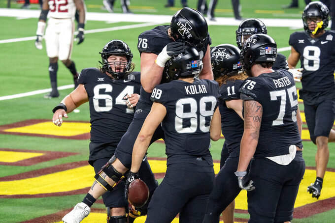 Iowa State tight end Charlie Kolar (88) is congratulated by offensive linemen Joey Ramos (76), Derek Schweiger (64), and Sean Foster (75) after his touchdown reception against Oklahoma during the first half of the the Big 12 Conference championship NCAA college football game, Saturday, Dec. 19, 2020, in Arlington, Texas. (AP Photo/Jeffrey McWhorter)