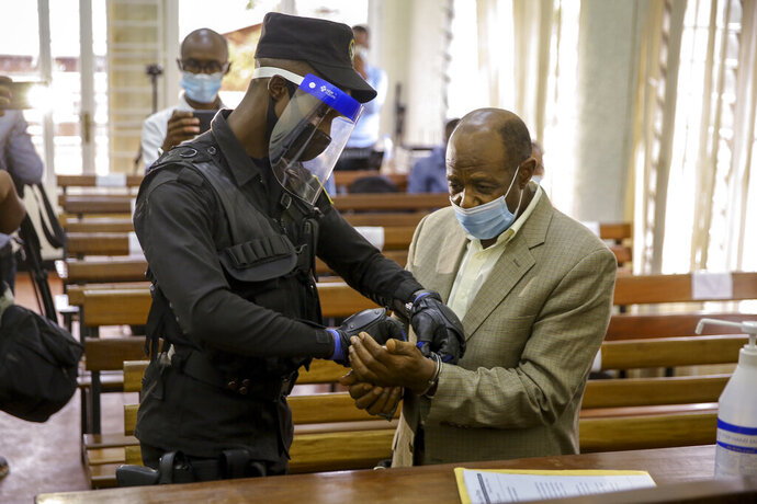 A policeman handcuffs Paul Rusesabagina, right, whose story inspired the film