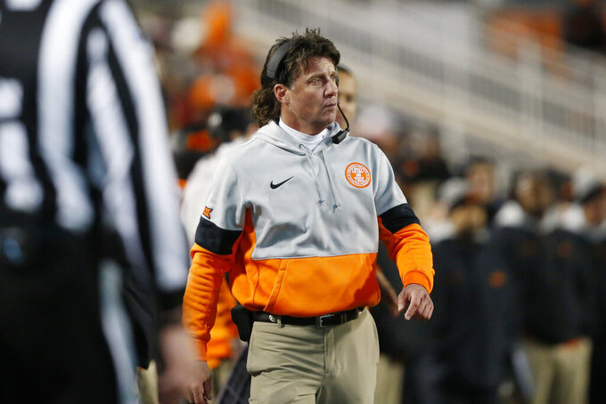 In this Nov. 30, 2019 file photo Oklahoma State head coach Mike Gundy walks on the sidelines during an NCAA college football game against Oklahoma in Stillwater, Okla. Gundy said Tuesday, April 7, 2020 he hopes to have his team return to its facilities on May 1, a proposed timetable that would defy federal social-distancing guidelines and was quickly disputed by the university and its athletic director. (AP Photo/Sue Ogrocki)