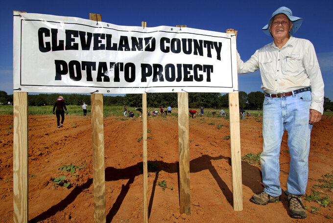 CEO Doug Sharp poses with the sign for the Cleveland County Potato Project Saturday, Sept. 4, 2021, in a potato field on Hamrick Road in Shelby, N.C. When Sharp founded the project 12 years ago, he had no idea his organization would reach more than 1 million pounds of distribution. Much of his ability to reach such an astronomical number stems from volunteers within the community. (Mike Hensdill/The Gaston Gazette via AP)