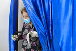 A woman wearing a mask to protect against COVID-19 infection exits a voting cabin in Bucharest, Romania, Sunday, Sept. 27, 2020. Polls have opened in Romania's municipal election, which is being seen as a test of how the next general election on Dec. 6 will unfold for the country's minority-led government.  (AP Photo/Andreea Alexandru)