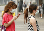FILE - In this Jan. 2, 2020, file photo, pedestrians wear masks as smoke shrouds the Australian capital of Canberra, Australia. It's an unprecedented dilemma for Australians accustomed to blue skies and sunny days that has raised fears for the long-term health consequences if prolonged exposure to choking smoke becomes the new summer norm. (AP Photo/Mark Baker, File)