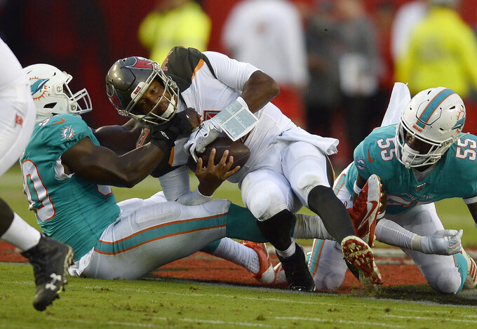 Miami Dolphins defensive end Charles Harris (90) and outside linebacker Jerome Baker (55) team up to sack Tampa Bay Buccaneers quarterback Jameis Winston (3) during the first half of an NFL preseason football game Friday, Aug. 16, 2019, in Tampa, Fla. (AP Photo/Jason Behnken)