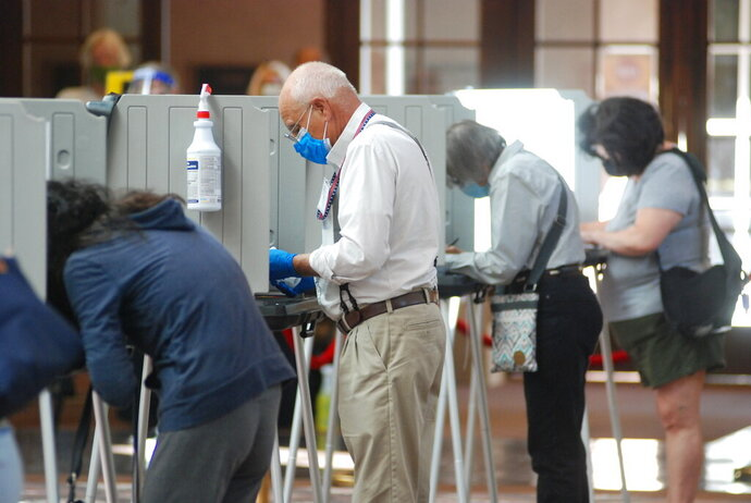 Temporary election worker Joseph Banar, center, disinfects voting stations as a precaution against the coronavirus while a steady stream of voters participates in the first day of balloting in New Mexico, at the Santa Fe Convention Center on Tuesday, Oct. 6, 2020, in Santa Fe, N.M. Election officials also are witnessing a massive surge in absentee ballot requests. (AP Photo/Morgan Lee)