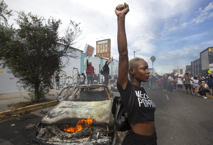 FILE - In this Saturday, May 30, 2020 file photo, a protester poses for photos next to a burning police vehicle in Los Angeles during a demonstration over the death of George Floyd. a black man who was killed in police custody in Minneapolis on May 25. (AP Photo/Ringo H.W. Chiu)