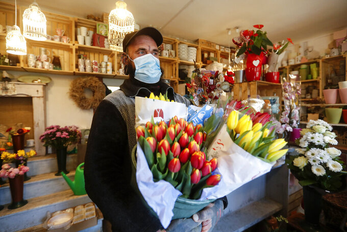 A staff member of a flower shop holds tulips in Budapest, Hungary, Wednesday April 7, 2021. Hungary's government lifted several lockdown restrictions on Wednesday, even as some doctors and medical experts urged caution after a record-breaking day of COVID-19 deaths, a move that came as Hungary reached 2.5 million first-dose vaccinations, a benchmark the government set for when a gradual reopening could move forward. (AP Photo/Laszlo Balogh)