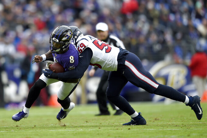 Baltimore Ravens quarterback Lamar Jackson (8 runs with the ball as Houston Texans outside linebacker Whitney Mercilus (59) makes the tackle during the first half of an NFL football game, Sunday, Nov. 17, 2019, in Baltimore. (AP Photo/Gail Burton)