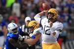 West Virginia quarterback Austin Kendall (12) passes to a teammate during the first half of an NCAA college football game against Kansas in Lawrence, Kan., Saturday, Sept. 21, 2019. Kendall passed for 202 yards in the game. West Virginia defeated Kansas 29-24. (AP Photo/Orlin Wagner)
