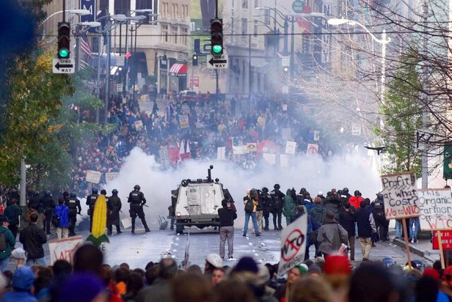 FILE - In this Nov. 30 1999, file photo, Seattle police use tear gas to push back World Trade Organization protesters in downtown Seattle. Seattle has a long history of demonstrations, stretching back to labor movements before World War I. (AP Photo/Eric Draper, File)