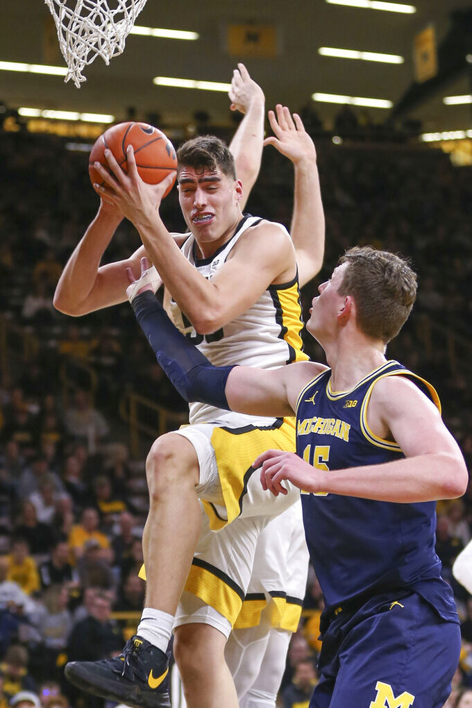Iowa center Luka Garza (55) grabs a rebound under pressure from Michigan center Jon Teske (15) during the first half of an NCAA college basketball game Friday, Jan. 17, 2020, in Iowa City, Iowa. (Rebecca F. Miller/The Gazette via AP)