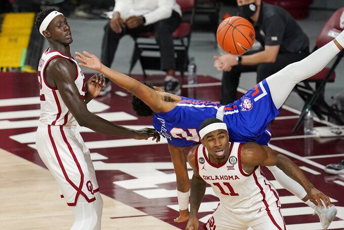 Houston Baptist guard Za-Ontay Boothman (2) lands on Oklahoma guard De'Vion Harmon (11) after reaching for a rebound in front of Oklahoma forward Kur Kuath, left, in the first half of an NCAA college basketball game Saturday, Dec. 19, 2020, in Norman, Okla. (AP Photo/Sue Ogrocki)