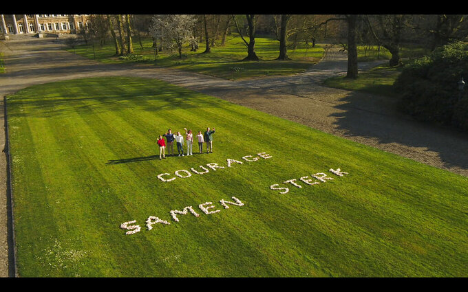 In this image from VTM video, Belgium's King Philippe, right, stands with members of his family in the Royal Gardens of Laeken with a message 'Courage, strong together' written on the lawn on April 4, 2020. In a pandemic time rife with restrictions, demands to respect social distancing have become quasi impossible to respect in public parks. One family in town though, has a lush garden all its own and ever more voices are being raised that the Royal Family of King Philippe should loosen up and open up at least part of their Park of Laeken to the public. (VTM via AP)