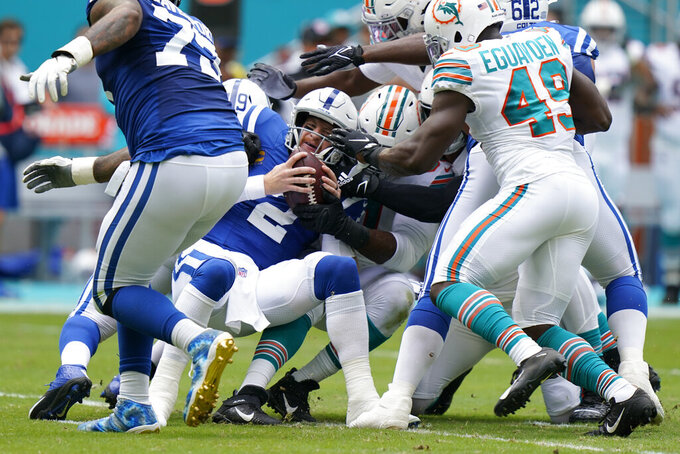 Indianapolis Colts quarterback Carson Wentz (2), center, gets sacked during the first half of an NFL football game against the Miami Dolphins, Sunday, Oct. 3, 2021, in Miami Gardens, Fla. (AP Photo/Lynne Sladky)