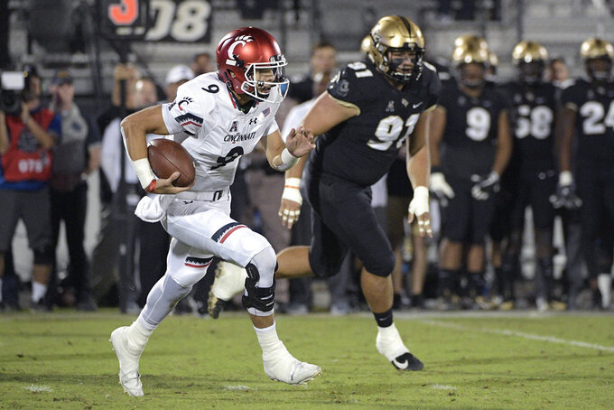 Cincinnati quarterback Desmond Ridder (9) scrambles for yardage in front of Central Florida defensive lineman Joey Connors (91) during the first half of an NCAA college football game Saturday, Nov. 17, 2018, in Orlando, Fla. (AP Photo/Phelan M. Ebenhack)