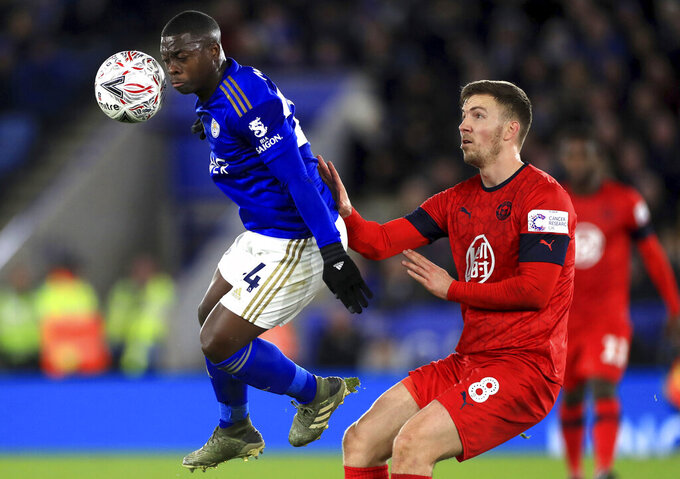 Wigan Athletic's Lee Evans, right, and Leicester City's Nampalys Mendy battle for the ball during their English FA Cup third round soccer match at The King Power Stadium, Leicester, England, Saturday, Jan. 4 2020. (Mike Egerton/PA via AP)