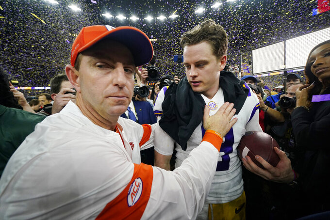 Clemson head coach Dabo Swinney, left, meets LSU quarterback Joe Burrow on the field after a NCAA College Football Playoff national championship game Monday, Jan. 13, 2020, in New Orleans. LSU won 42-25. (AP Photo/David J. Phillip)