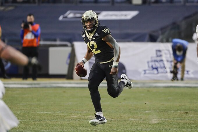 Wake Forest's Jamie Newman (12) rushes during the first half of the Pinstripe Bowl NCAA college football game against Michigan State, Friday, Dec. 27, 2019, in New York. (AP Photo/Frank Franklin II)