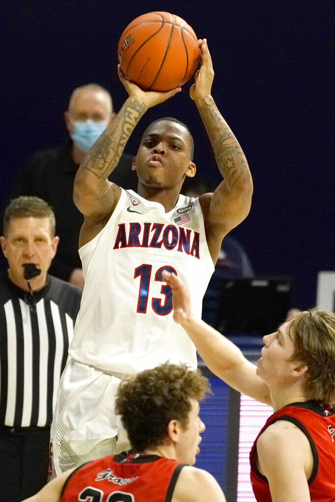 Arizona guard James Akinjo (13) shoots over Eastern Washington guard Jacob Groves (33) and Jack Perry (11) during the first half of an NCAA college basketball game, Saturday, Dec. 5, 2020, in Tucson, Ariz. (AP Photo/Rick Scuteri)