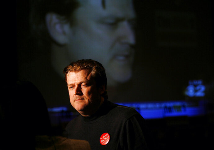"FILE - In this Nov. 6, 2007, file photo Patrick Byrne, President and CEO of Overstock.com is reflected on a large television screen while being interviewed at the headquarters for supporters of school vouchers in Salt Lake City. Byrne has resigned, saying he'd become ""far too controversial"" to helm the e-commerce company known for selling discounted sofas and jewelry. Bryne, who founded the online discount retailer 20 years ago, said Thursday, Aug. 22, 2019, that was ""in the sad position"" of having to step down. (AP Photo/Steve C. Wilson)"