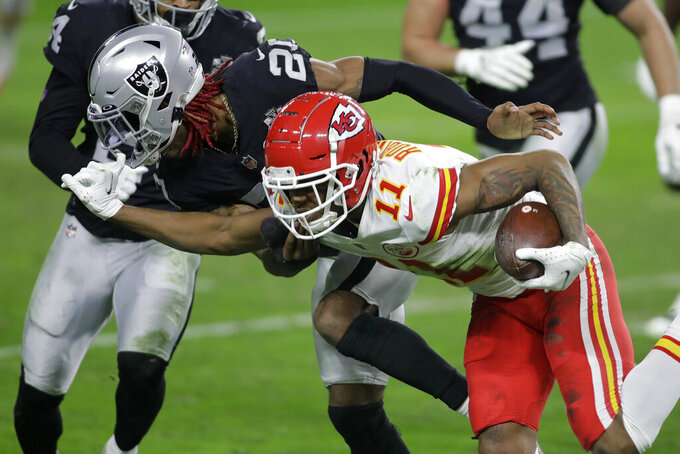 Kansas City Chiefs wide receiver Demarcus Robinson (11) grabs the facemask of Las Vegas Raiders cornerback Damon Arnette (20) during the first half of an NFL football game, Sunday, Nov. 22, 2020, in Las Vegas. (AP Photo/Isaac Brekken)
