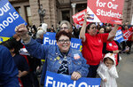 In this March 11, 2019, photo, Dr. Nancy Vera, center, of Corpus Christi, Texas, joins other educators during a rally to support funding for public schools in Texas at the state Capitol in Austin, Texas. Cost-cutting states are trying to keep schools happy as teacher unrest over low pay and overcrowded classrooms continues. But pressure from voters is forcing states to put more money on the table as much as much as picket lines. (AP Photo/Eric Gay)