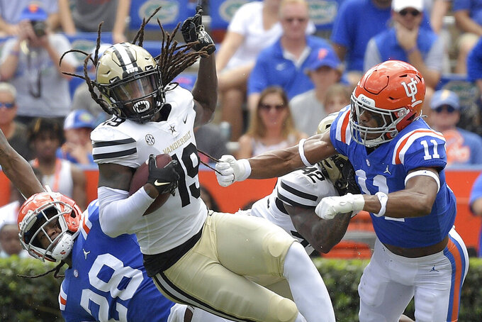 Vanderbilt wide receiver Chris Pierce Jr. (19) is tackled by Florida linebackers Ty'Ron Hopper (28) and Mohamoud Diabate (11) after catching a pass during the first half of an NCAA college football game, Saturday, Oct. 9, 2021, in Gainesville, Fla. (AP Photo/Phelan M. Ebenhack)