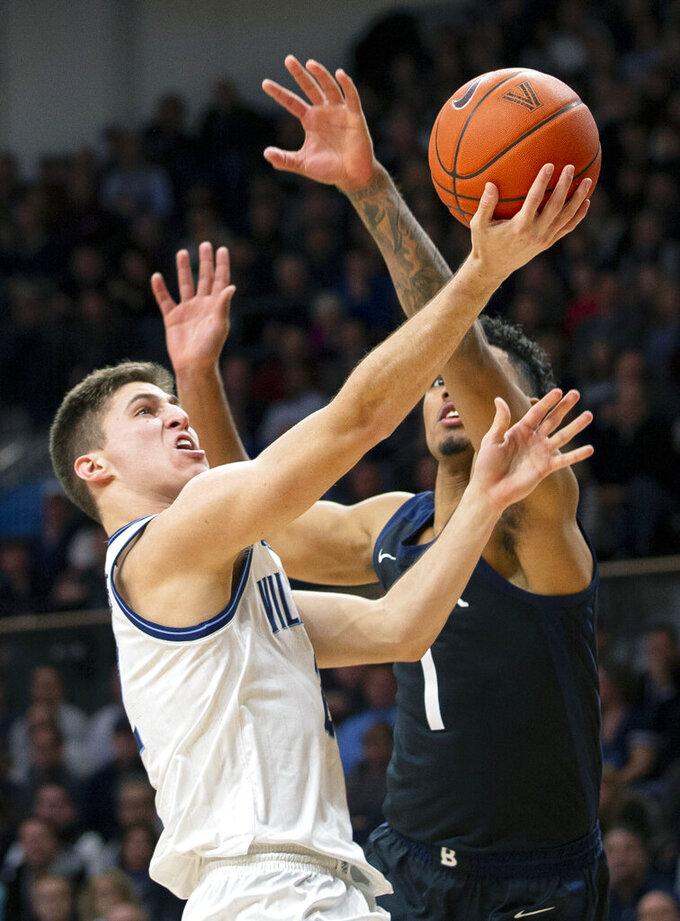 Villanova guard Collin Gillespie (2) takes a shot past Butler forward Jordan Tucker (1) during the first half of an NCAA college basketball game, Tuesday, Jan. 21, 2020, in Villanova, Pa. (AP Photo/Laurence Kesterson)