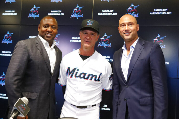 Miami Marlins manager Don Mattingly, center, poses with president of baseball operations Michael Hill, left, and CEO Derek Jeter, right, after a news conference Friday, Sept. 20, 2019, in Miami. Mattingly will be back with the Marlins in 2020. His contract extension announced Friday is for two years, plus a mutual option for a third year in 2022. (AP Photo/Wilfredo Lee)