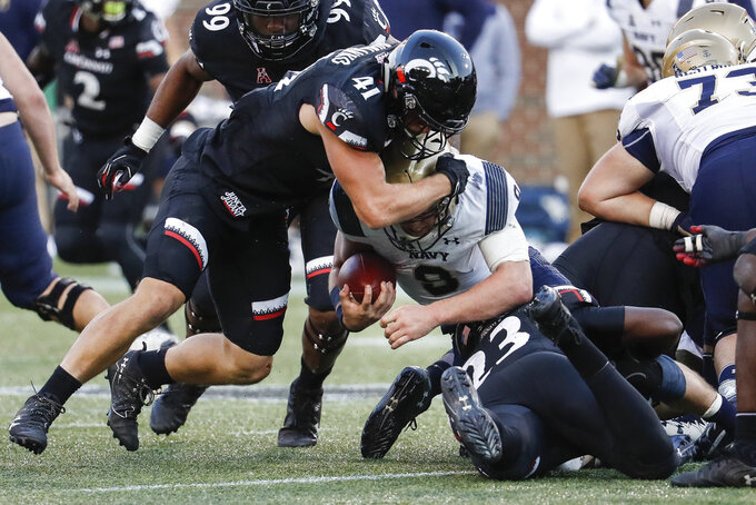 Navy wide receiver Zach Abey, center, is tackled by Cincinnati linebacker Joel Dublanko (41) and linebacker RJ Potts (23) in the second half of an NCAA college football game, Saturday, Nov. 3, 2018, in Cincinnati. (AP Photo/John Minchillo)