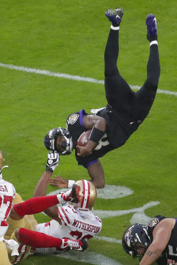 Baltimore Ravens quarterback Lamar Jackson (8) flips after being tripped by San Francisco 49ers cornerback Ahkello Witherspoon (23) in the first half of an NFL football game, Sunday, Dec. 1, 2019, in Baltimore, Md. (AP Photo/Julio Cortez)