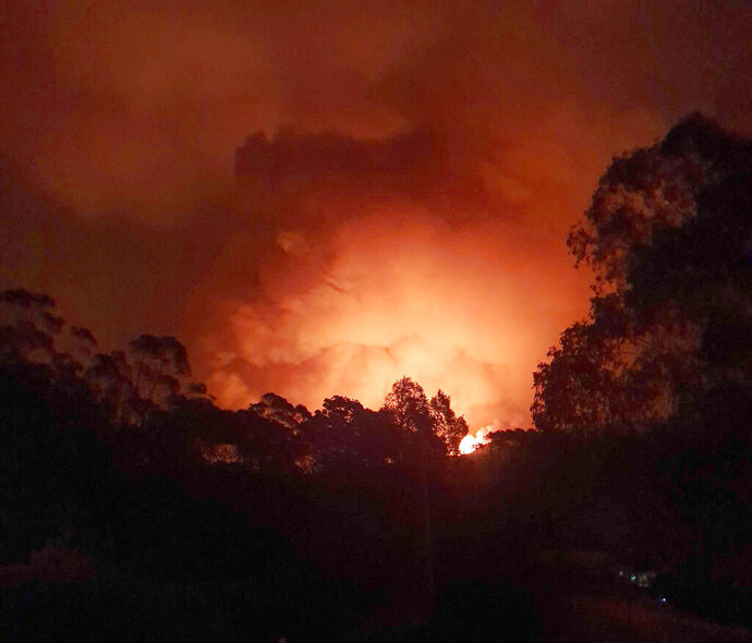 In this Dec. 31, 2019, photo provided by Siobhan Threlfall, a fire approaches the village of Nerrigundah, Australia. The tiny village has been among the hardest hit by Australia's devastating wildfires, with about two thirds of the homes destroyed and a 71-year-old man killed. (AP Photo/Siobhan Threlfall)