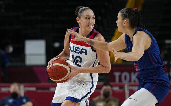 United States' Diana Taurasi (12) drives around Serbia's Sasa Cado (6) during women's basketball semifinal game at the 2020 Summer Olympics, Friday, Aug. 6, 2021, in Saitama, Japan. (AP Photo/Eric Gay)