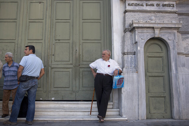 FILE - In this Tuesday, June 14, 2015 file photo, pensioners stand outside the main gate of the National bank of Greece, in Athens. A high court in Greece has ruled on Tuesday, July 14, 2020, in favor of retirees in a class action case in which they demanded the reimbursement of money cut from their income during international bailouts.(AP Photo/Petros Giannakouris, file)