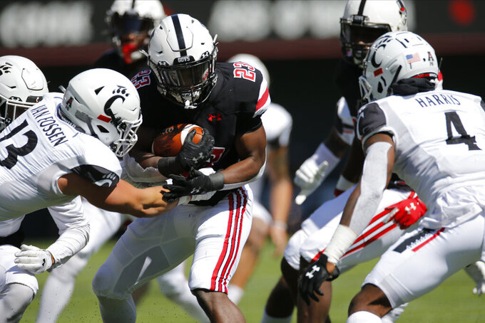 Austin Peay running back CJ Evans, center, is stopped near the line of scrimmage by Cincinnati linebacker Ty Van, left, and defensive back Justin Harris during the first half of an NCAA college football game Saturday, Sept. 19, 2020, in Cincinnati, Ohio. (AP Photo/Jay LaPrete)