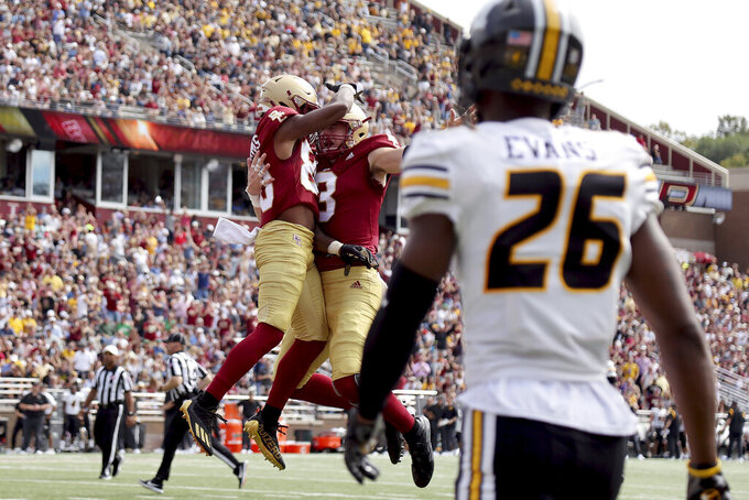 Boston College wide receiver Jaden Williams (80) is congratulated by quarterback Dennis Grosel (8) after scoring a touchdown as Missouri defensive back Akayleb Evans (26) looks on during the first half of an NCAA college football game, Saturday, Sept. 25, 2021, in Boston. (AP Photo/Mary Schwalm)