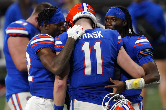 Florida players console Florida quarterback Kyle Trask (11) after the Southeastern Conference championship NCAA college football game against Alabama, Saturday, Dec. 19, 2020, in Atlanta. Alabama won 52-46. (AP Photo/John Bazemore)