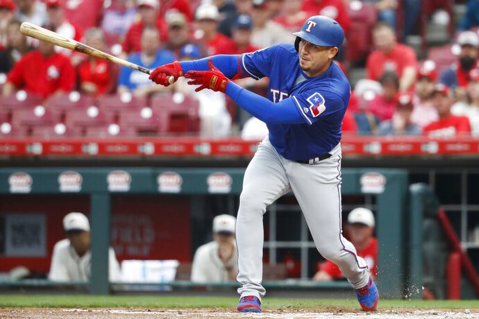 Texas Rangers' Asdrubal Cabrera hits an RBI single off Cincinnati Reds starting pitcher Tanner Roark during the first inning of a baseball game Saturday, June 15, 2019, in Cincinnati. (AP Photo/John Minchillo)
