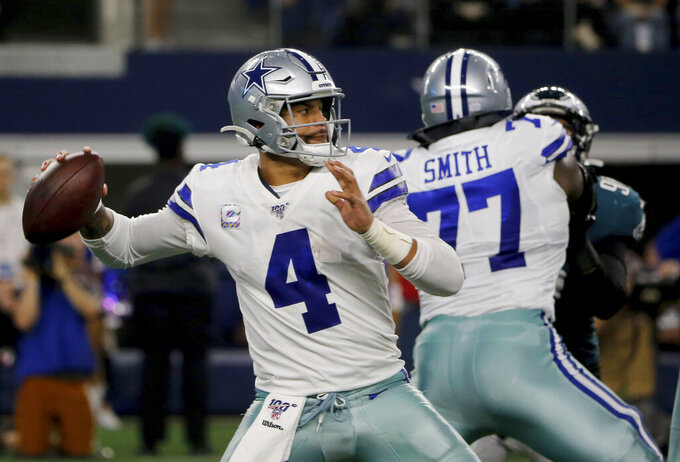 Dallas Cowboys quarterback Dak Prescott (4) throws a pass as offensive tackle Tyron Smith (77) provides protection in the first half of an NFL football game agains the Philadelphia Eagles in Arlington, Texas, Sunday, Sunday, Oct. 20, 2019. (AP Photo/Michael Ainsworth)