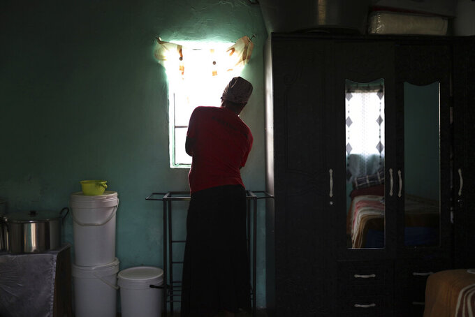 """Matefo Litali opens the curtains of her small rented room that she shares with her youngest daughter and a granddaughter, in the town of Ha Thetsane, Maseru, Lesotho, on Friday, Dec. 11, 2020. While she waited for her final paycheck after being laid off, Litali received no income or support for three months. The family survived off food parcels donated by the local church until her salary arrived. """"I got so stressed I thought I was going mad,"""" she explains. """"I would spend the whole day in my house sleeping, not doing anything. It got to a stage where I wouldn't even try to talk with my daughter. She would ask me: 'Are you sick? What is the problem?' and I wouldn't say anything to her. I didn't want to speak to anyone or ask for help."""" (Neo Ntsoma/The Fuller Project via AP)"""