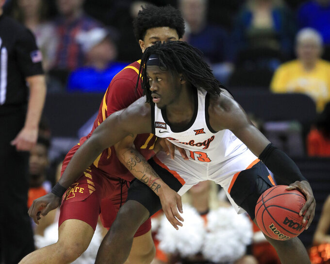 Oklahoma State guard Isaac Likekele (13) is covered by Iowa State guard Prentiss Nixon, left, during the second half of an NCAA college basketball game in the first round of the Big 12 men's basketball tournament in Kansas City, Kan., Wednesday, March 11, 2020. Oklahoma State defeated Iowa State 72-71. (AP Photo/Orlin Wagner)