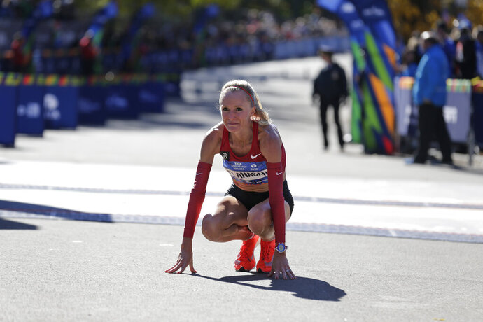FILE - In this Nov. 4, 2018 file photo Shalane Flanagan of the United States reacts after crossing the finish line third in the women's division of the New York City Marathon in New York. Flanagan says she is retiring from competitive running to become a coach. She made the announcement Monday, Oct. 21, 2019 saying she has only one regret: