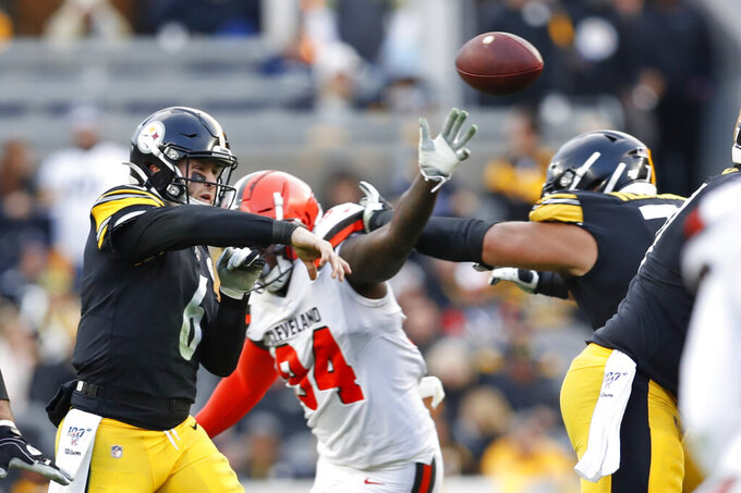 Pittsburgh Steelers quarterback Devlin Hodges (6) passes the ball as he is pressured by Cleveland Browns defensive end Bryan Cox (94) in the second half of an NFL football, Sunday, Dec. 1, 2019, in Pittsburgh. (AP Photo/Don Wright)