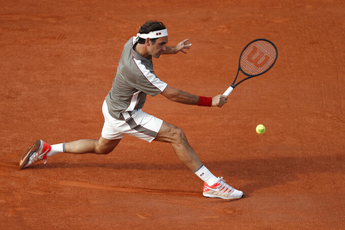 "FILE- In this Tuesday June 4, 2019, image, Switzerland's Roger Federer plays a shot against Switzerland's Stan Wawrinka during their quarterfinal match of the French Open tennis tournament at the Roland Garros stadium in Paris. The skill of sliding at Roland Garros is on hold at the moment with the start of the French Open postponed until September because of the coronavirus, but sliding will still be one of the keys to success at the French Open whenever it is played. Federer returned to clay-court tennis in 2019, a decade after his French Open title with his confidence low, he explained, ""because I don't even remember how to slide anymore."" (AP Photo/Jean-Francois Badias, File)"