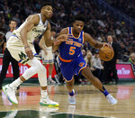 New York Knicks' Dennis Smith Jr. (5) drives against Milwaukee Bucks' Giannis during the first half of an NBA basketball game Monday, Dec. 2, 2019, in Milwaukee. (AP Photo/Jeffrey Phelps)